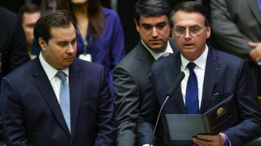 Bolsonaro faz o juramento de cumprimento à Constituição, ao lado de Rodrigo Maia