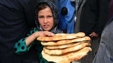 A young girl receives free bread from the municipality during Ramadan as the government-imposed a nationwide lockdown, in Kabul on April 29, 2020