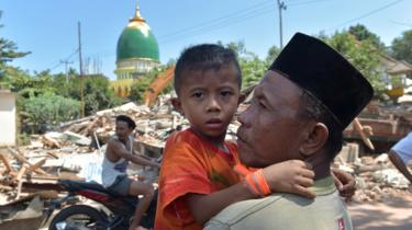 An Indonesian man holds a boy across from collapsed buildings as search and rescue members search for a victim of the recent quake in Tanjung on Lombok island on August 9, 2018.