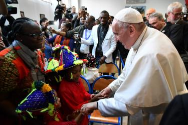 Pope Francis greets children during his visit to a centre run by the Catholic humanitarian organisation Caritas, which hosts migrants, in the Moroccan capital Rabat, 30 March