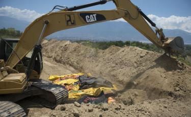 Bodies in body bags lie next to a digger in a mass grave in Palu