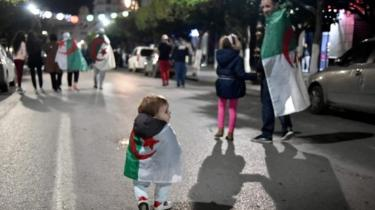 A small child draped in Algeria's national flag celebrates in Algiers. Photo: 2 April 2019