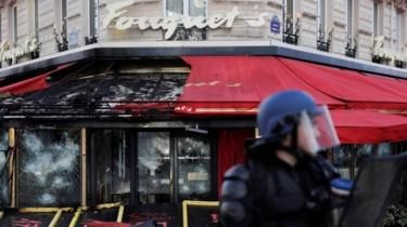 A French riot police officer stands in front of the gutted Le Fouquet's restaurant in Paris. Photo: 16 March 2019