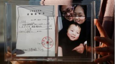 Li Wenzu, the wife of prominent Chinese rights lawyer Wang Quanzhang, holds a box with a family picture and her husband's detention notice, before shaving her head in protest in Beijing, China