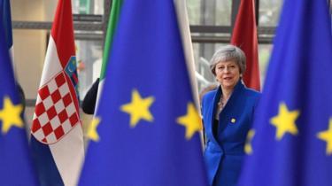 Theresa May standing behind EU flags