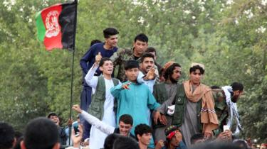 Taliban militants and soldiers mingle with residents of Kunduz during the Eid ceasefire