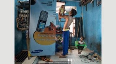 Rizwan Shaikh dan anak perempuannya di rumah mereka di permukiman kumuh Wadala di Mumbai, India; dia berharap anak perempuannya yang berusia tiga tahun, Zafinah, akan menjadi dokter.