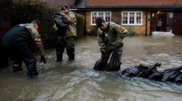 A woman looks from the door of her flooded home as soldiers place sandbags on her driveway in Wraysbury, near London. Photo: February 2014