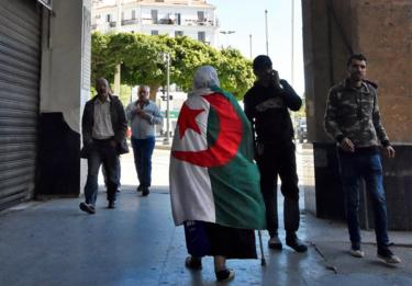 An elderly Algerian woman wrapped in a national flag walks through a colonnade in Algiers.