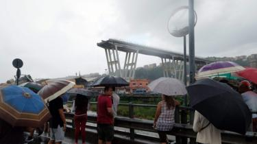 People gather to watch the rescue operation after a section of a giant motorway bridge collapsed, on August 14, 2018 in Genoa