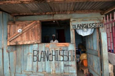 "A man is seen inside a wooden structure that has signs saying ""blanchisserie"", the French word for laundry, daubed in paint on the outside in Abidjan, Ivory Coast - Tuesday 19 February 2019"