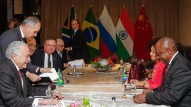 Em encontro bilateral, imagem mostra Michel Temer sentado em frente ao presidente da África do Sul, Cyril Ramaphosa, com ministros e outras pessoas à mesa, durante cúpula dos Brics, em Joanesburgo.