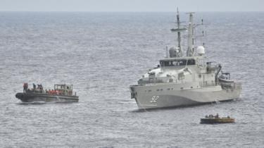 An Australian Navy vessel pictured beside an asylum seeker boat