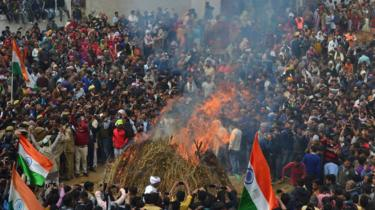 Mourners gather to watch the cremation at the funeral for Indian Central Reserve Police Force (CRPF) trooper Kaushal Kumar Rawat in Agra
