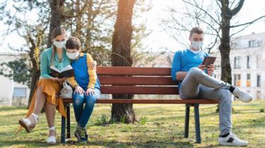 Una mujer con un niño y uno hombre sentados separados en un banco de plaza. Todos con mascarilla.