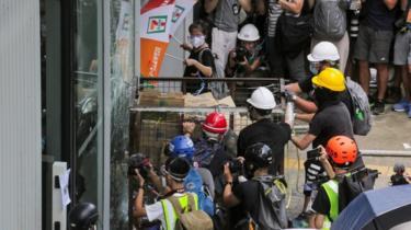 manifestantes intentan ingresar a un edificio