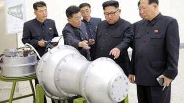 Le président Nord Coréen Kim Jong-un discute avec ses associés devant ce qui apparait comme la bombe à hydrogène