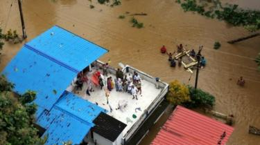 People wait for aid on the roof of their house at a flooded area in the southern state of Kerala, India, on 17 August 2018.