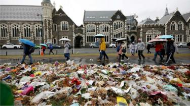 People walk past flowers and tributes displayed in memory of the twin mosque massacre victims outside the Botanical Gardens in Christchurch