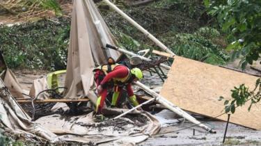 A rescuer checks damaged tents in Saint-Julien-de-Peyrolas, southern France. Photo: 9 August 2018