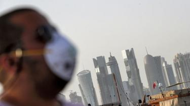 Man wearing a facemask with the Doha skyline in the background