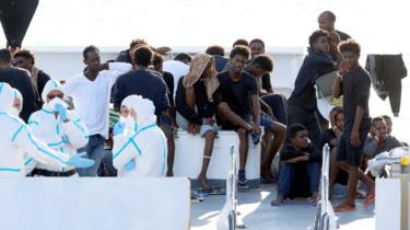 Migrants wait to disembark from the Italian coast guard vessel Diciotti at the port of Catania, Italy, August 22, 2018