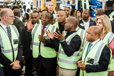 President Ramaphosa and Volvo staff in high-viz jackets on the factory floor