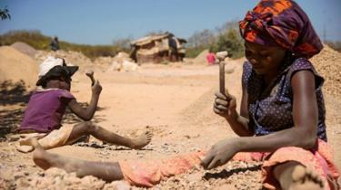 une jeune femme et un enfant concassent des pierres extraites d'une mine à la recherche de cobalt