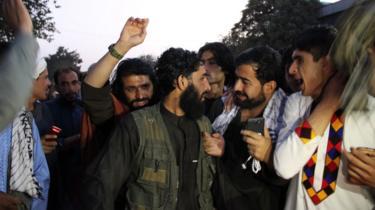 Taliban members speak to residents in Kunduz