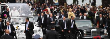King Mohammed VI (R) waves to the crowd from his car as he arrives with Pope Francis (L) the pontiff's arrival