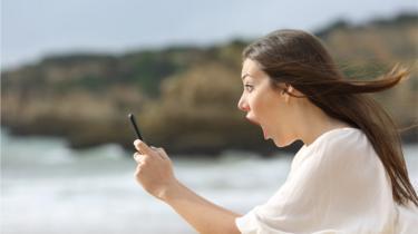 Mulher de boca aberta olhando um celular que tem na mão