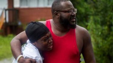 Warga melihat warga lain diselamatkan setelah sebuah pohon rubuh di rumahnya di Wilmington, North Carolina.