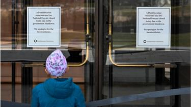 A young girl reads a sign posted on the door of The National Museum of African American History stating that all Smithsonian Museums are closed due to the partial shutdown of the US government