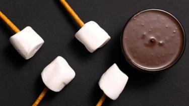 Palitos com marshmallow ao lado de pote de chocolate