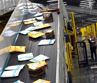 Customer orders are carried on a conveyor system at the newest Amazon Robotics fulfillment center during its first public tour on April 12, 2019 in the Lake Nona community of Orlando, Florida.