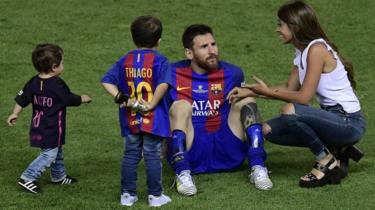 Lionel Messi joined on the pitch by Antonela Roccuzzo and their two sons