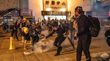 Protesters put out the tear gas as they pour water on it at Kwai Fong district