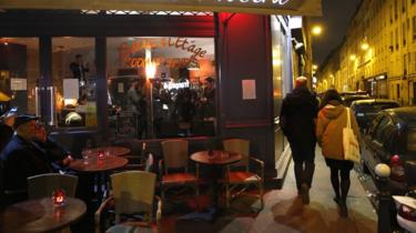 Two people walk down the path outside a restaurant, while two more sit on the exterior seating of the cafe / restaurant in Paris