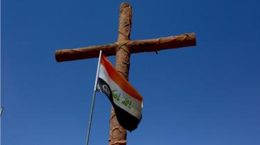 Cross with Iraqi flag at entrance to Christian town of Qaraqosh