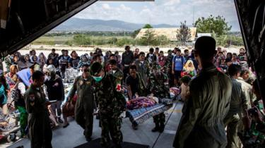 Soldiers watch as people board a military plane at Palu airport