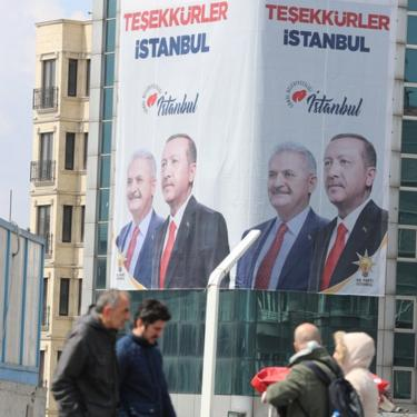 "People pass in front of a huge banner with pictures of Turkish President Recep Tayyip Erdogan and Binali Yildirim, candidate of Turkish ruling party Justice and Development Party (AK Party) reading on ""Thank you Istanbul"" in Istanbul, Turkey, 03 April 2019"