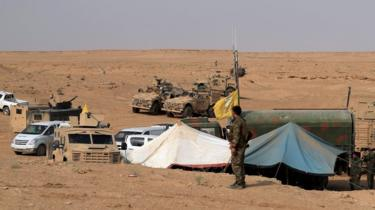 Coalition forces and members of the Syrian Democratic Forces (SDF) gather at their operation room near the village of Susah in the eastern province of Deir Ezzor