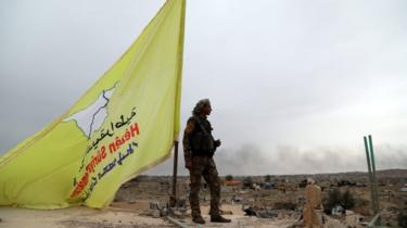 Fighter of the Syrian Democratic Forces (SDF) stands guard next to a yellow flag in Baghuz