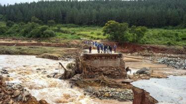 Timber company workers stand stranded on a damaged road on March 18, 2019, at Charter Estate, Chimanimani, eastern Zimbabwe