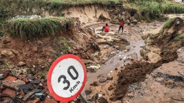 Pemba residents stand by a road partially destroyed by heavy flooding