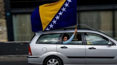 A man waves the Bosnian flag in Sarajevo on October 6, 2018
