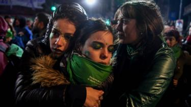 Pro-choice campaigners hug each other outside Argentina's parliament