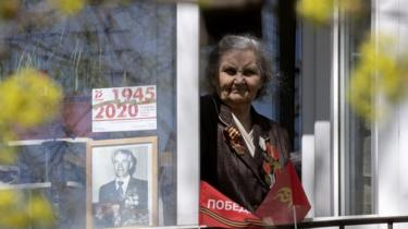 A woman displays a photo of a loved one in her window in St Petersburg, Russia