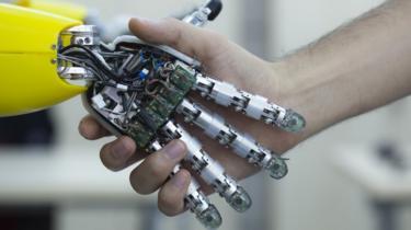 Man shaking robot hand