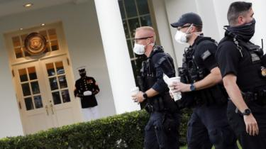 A Marine and members of US Secret Service are seen outside the West Wing following US President Donald Trump's return to the Oval Office in Washington, DC, 8 October 2020